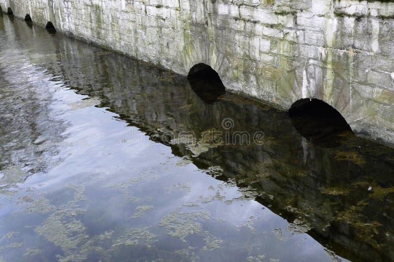 Мост сводов каменный в воде стоковая фотография