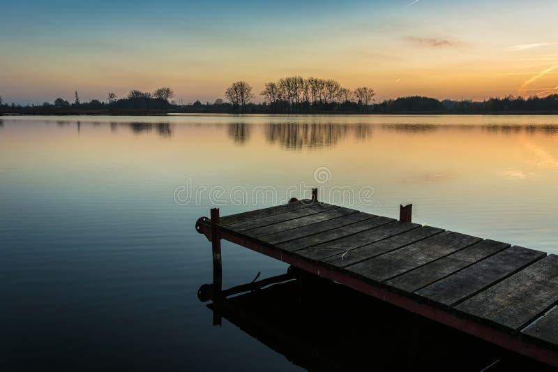 Мост сделанный планок на озере и небе после захода солнца стоковые фотографии rf