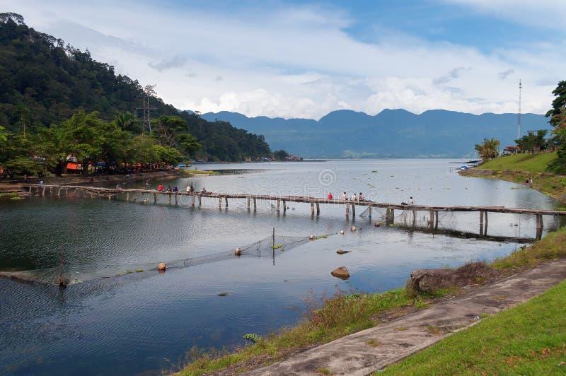 Мост с рыболовами на озере Maninjau стоковое фото rf
