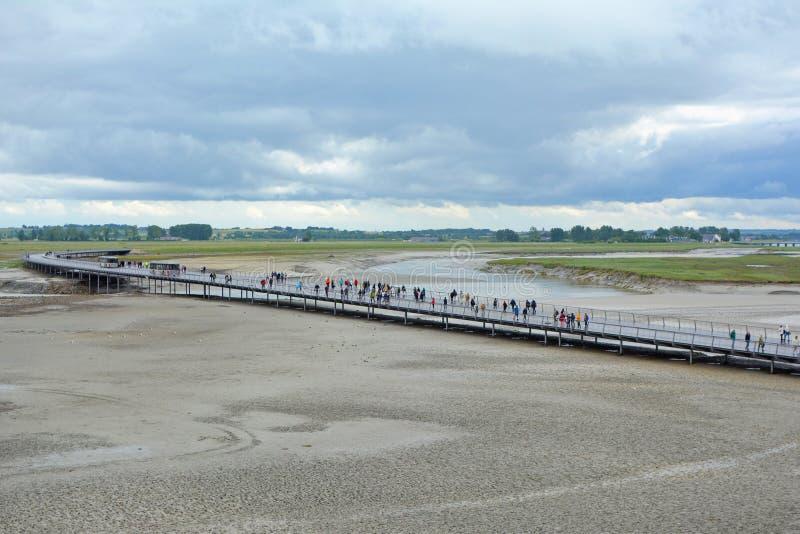 Мост с туристами водя к французской исторической видимости видя attracktion Le Mont Святого Мишеля над водой стоковые изображения rf
