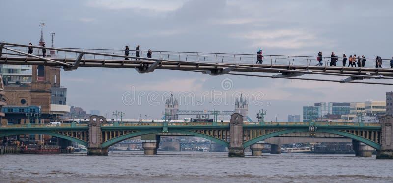 Мост тысячелетия в переднем плане с пешеходами идя поперек В мосте Southwark расстояния, и за этим мостом башни стоковые изображения rf