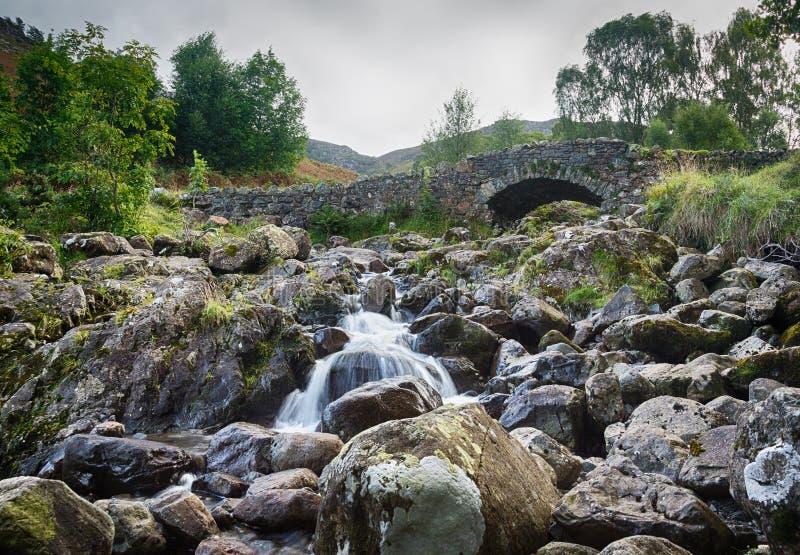 Мост Ashness над малым потоком в заречье озера стоковые фотографии rf