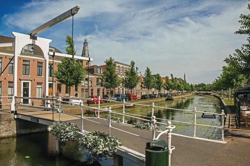 Мост Bascule над каналом с аквариумными растениами и домами кирпича на солнечный день в Weesp стоковое изображение
