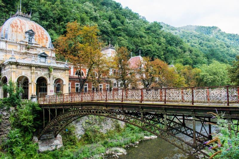 Мост n старый который пересекает реку, водя к старому загубленному дворцу, где-то в Европе, в деревьях зеленого цвета в августе и стоковое фото
