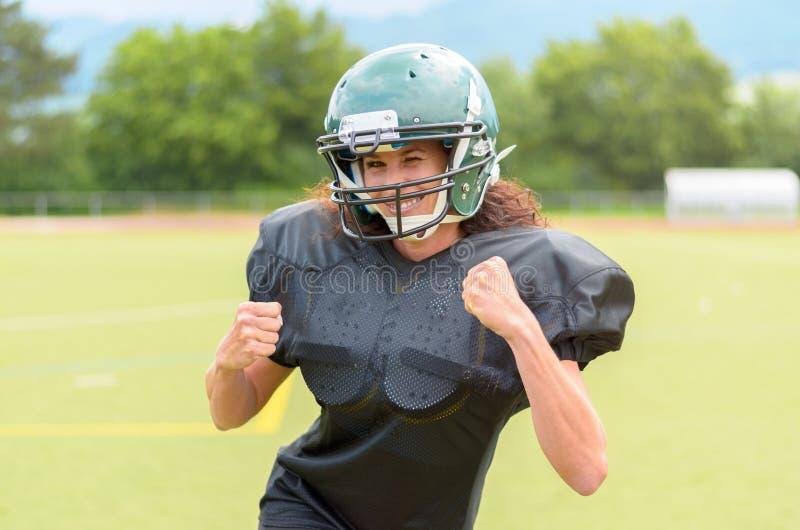Мотивированная молодая женщина играя американский футбол стоковая фотография