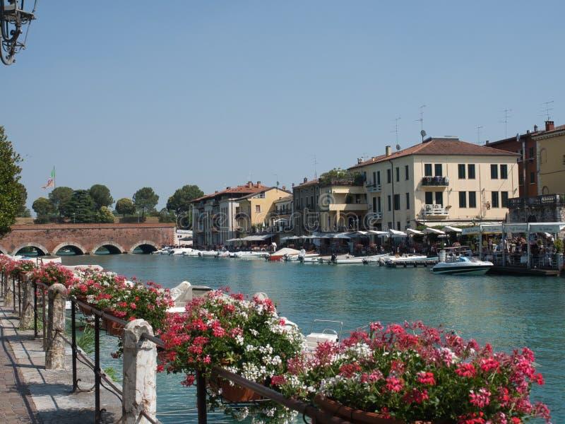 Моторки припаркованные вдоль канала del garda peschiera в garda озера, Италии с местными делами на заднем плане и цветках на стоковое изображение
