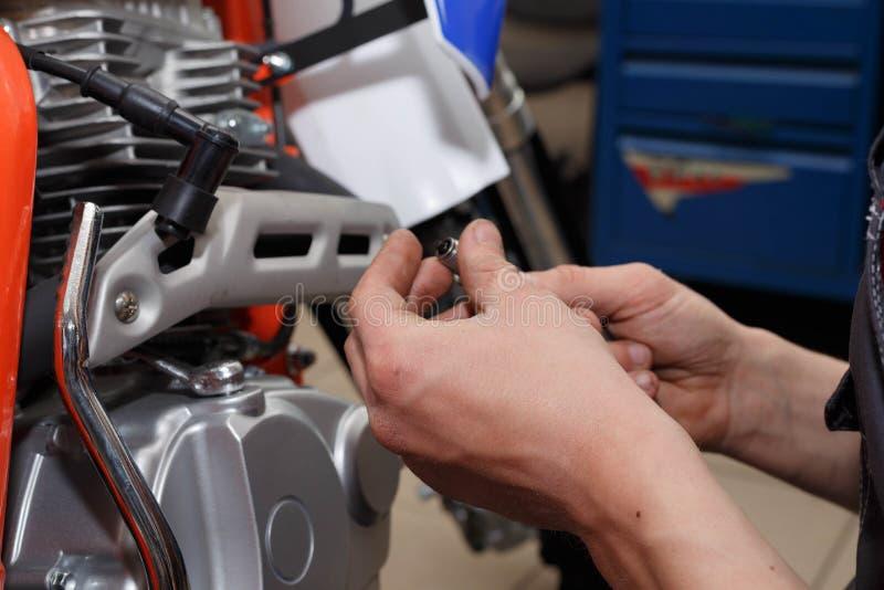 Мотоциклист заменяет, проверки свеча накаливания в мотоцикле стоковая фотография