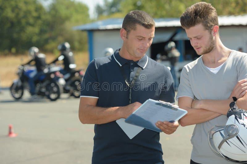 Мотоциклист имеет экзамен по вождению в школе moto для лицензии водителей стоковые изображения