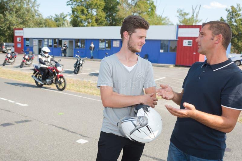 Мотоциклист около для того чтобы сделать экзамен по вождению в школе мотоцилк стоковые фото