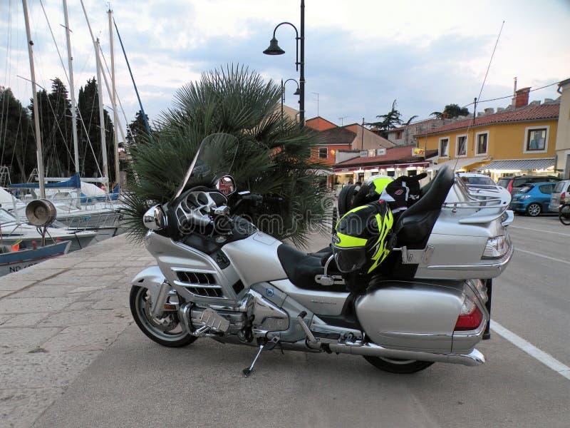 Мотоциклы с освещенными светами стоят в линии с камнями вымощенными в прибрежном городе Хорватии, праве рядом с Адриатическим мор стоковые фото
