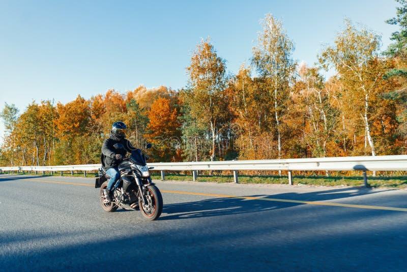 Мотоцикл катания водителя на пустой дороге в красивом лесе осени стоковое фото