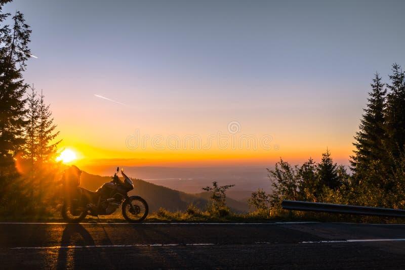 Мотоцикл приключения, мотоцикл силуэта touristic горные пики в темных цветах захода солнца скопируйте космос Концепция  стоковая фотография