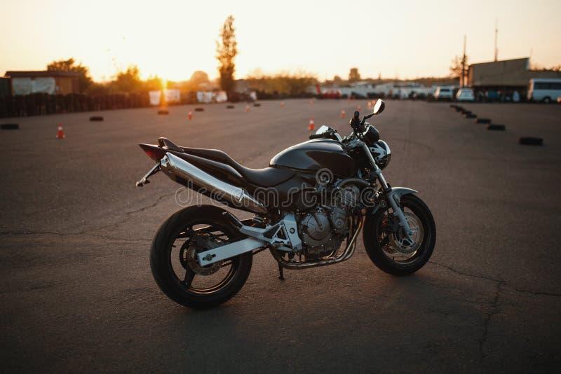 Мотоцикл стоит все еще на заходе солнца стоковые фотографии rf