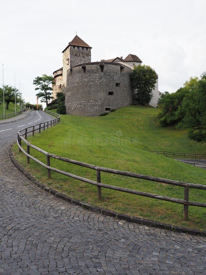 Мощенные булыжником дорога и замок в европейской столице Вадуц в Лихтенштейне - вертикали стоковое изображение rf