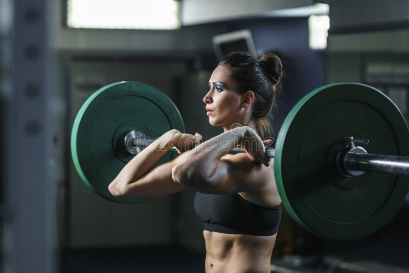 Мощный привлекательный мышечный тренер CrossFit женщины делает разминку с штангой стоковые изображения