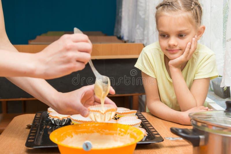 Моя дочь выглядеть как мама подготавливает пробел для печь торты пасхи стоковая фотография
