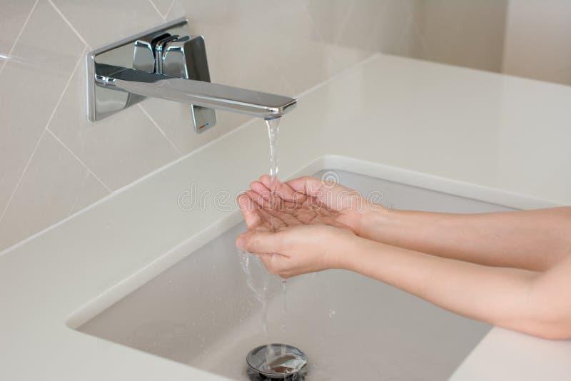 Моя руки и вода лить от крана стоковые фото