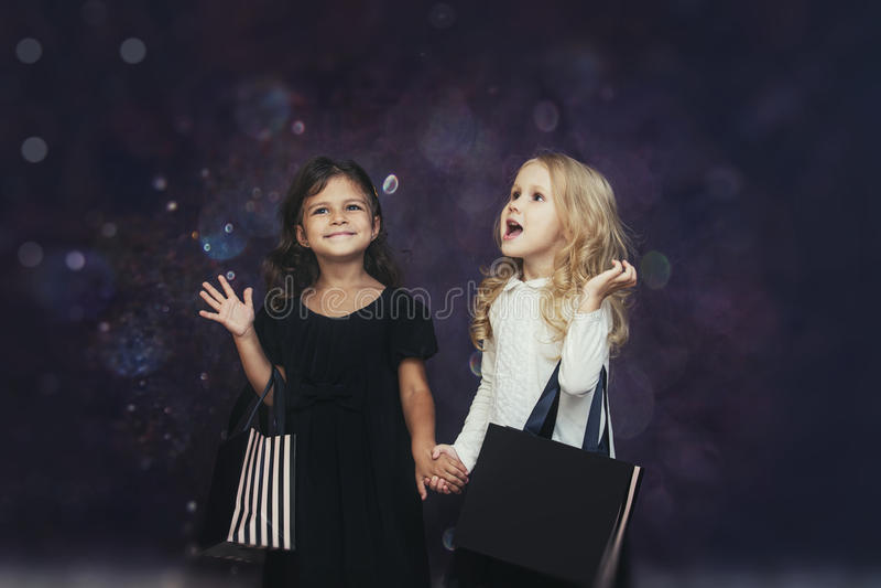 Мода ребенка маленьких девочек с бумажными сумками на предпосылке с стоковая фотография rf