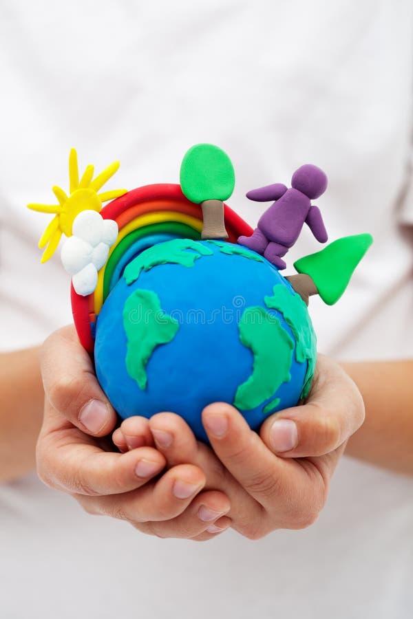 Моделирование земли глины с радугой и деревьев в руках ребенка стоковое фото