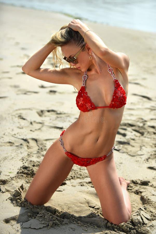 Моделируйте в красный представлять бикини сексуальный на пляже стоковое фото rf