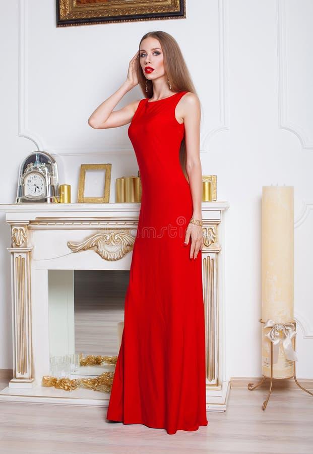 Моделируйте при красивые длинные волосы представляя в красном платье стоковые изображения