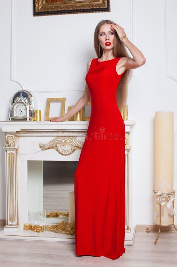 Моделируйте при красивые длинные волосы представляя в красном платье стоковое изображение rf