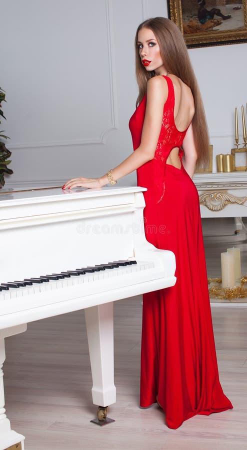 Моделируйте при красивые длинные волосы представляя в красном платье стоковая фотография rf