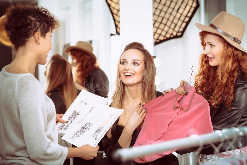 Модельеры и модель с одеждами стоковые изображения