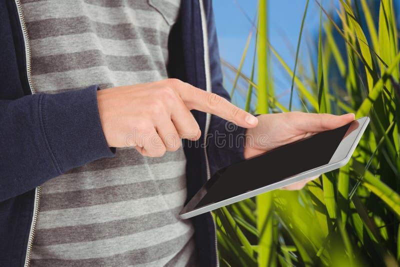 Модельный касающий экран планшета против предпосылки природы стоковое изображение