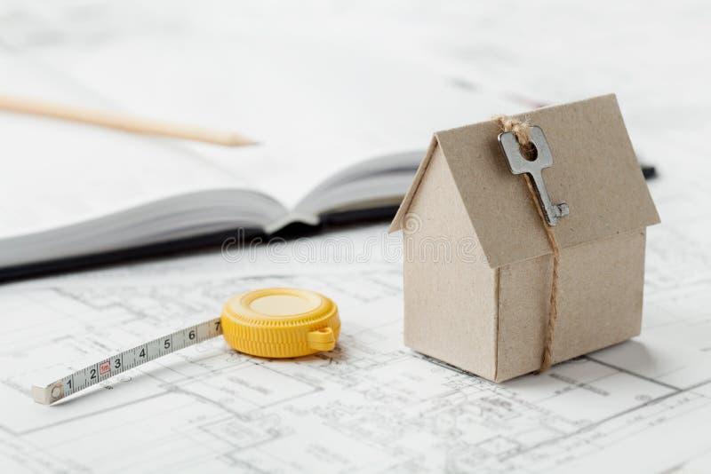 Модельный дом картона с ключом и рулеткой на светокопии Идея проекта жилищного строительства, архитектурноакустических и конструк стоковое изображение rf
