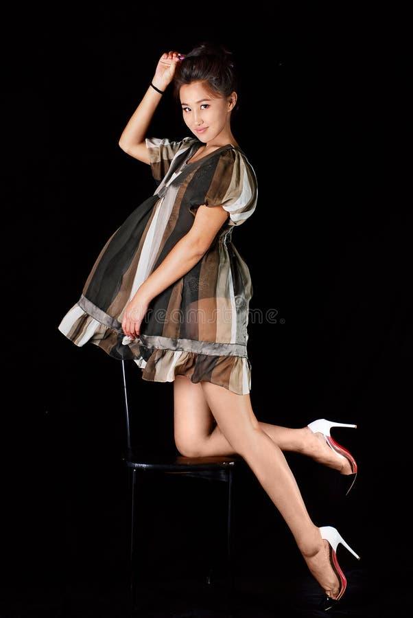 Модель в striped платье possing в студии Черная предпосылка, стоковые фотографии rf