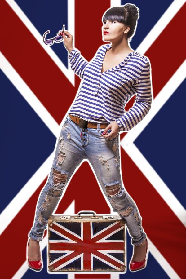 Модель женщина на великобританской предпосылке флага с чемоданом стоковая фотография