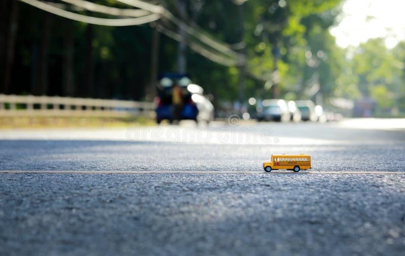 Модель игрушки школьного автобуса на дороге стоковая фотография rf