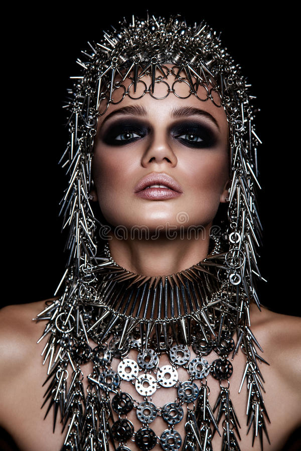 Модель красоты высокой моды с металлическим headwear и темным составом и голубые глазы на черной предпосылке стоковая фотография