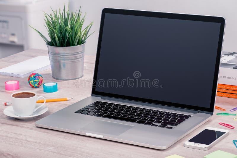 Модель-макет компьтер-книжки на столе офиса с smartphone и чашкой кофе стоковое фото