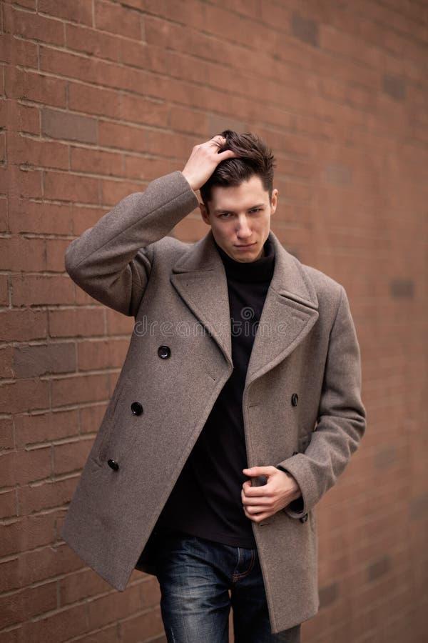 Модель молодого человека в пальто представляет на кирпичной стене. Тонизированный стоковые фото