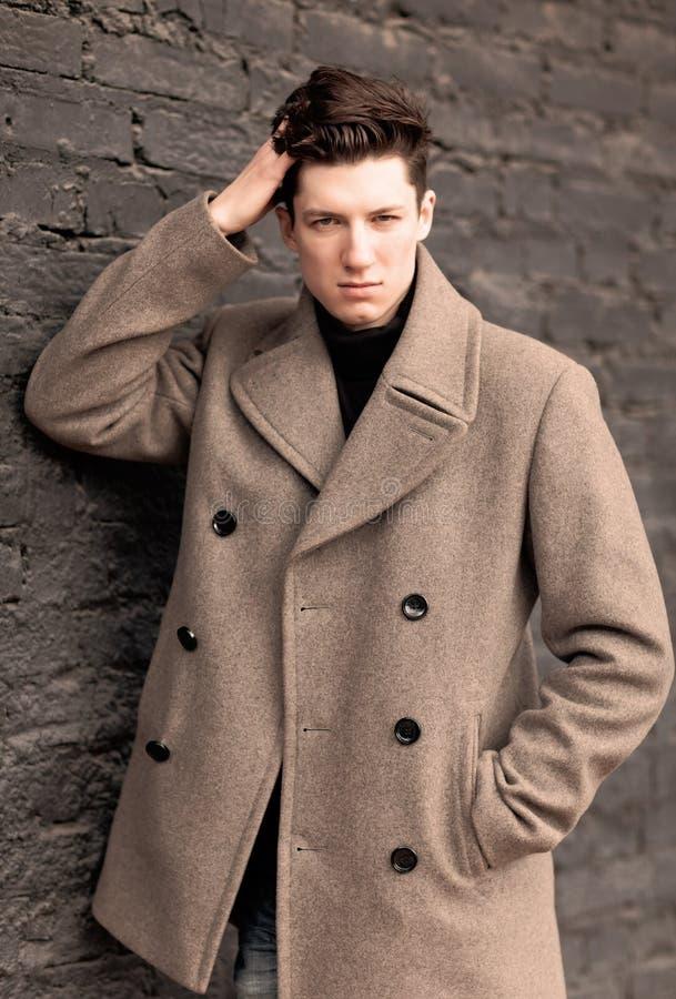 Модель молодого человека в пальто представляет на кирпичной стене. Тонизированный стоковое фото rf