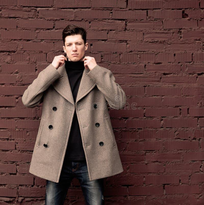 Модель молодого человека в пальто представляет на кирпичной стене. Тонизированный стоковое изображение rf