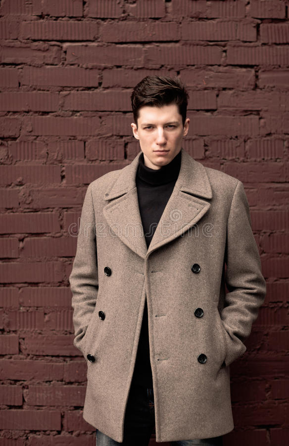 Модель молодого человека в пальто представляет на кирпичной стене. Тонизированный стоковое изображение
