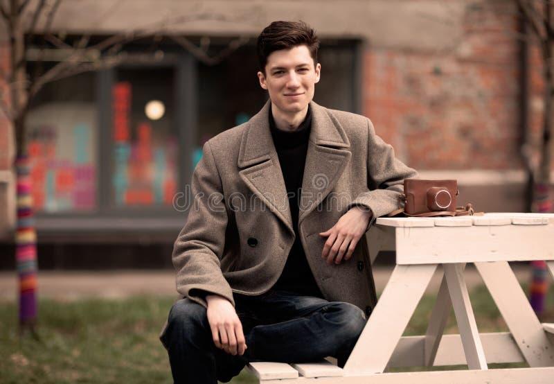 Модель молодого человека в пальто сидит на белой таблице с винтажной камерой outdoors стоковые изображения rf