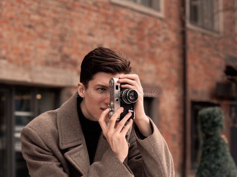 Модель молодого человека в пальто фотографирует винтажную камеру стоковая фотография