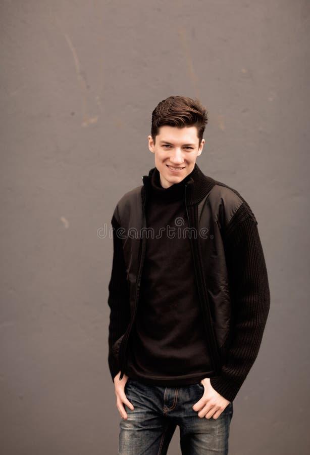 Модель молодого человека в черной куртке представляет на стене. тонизированное изображение стоковые фотографии rf