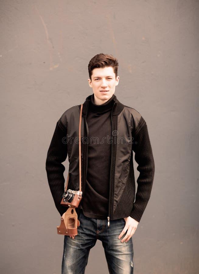 Модель молодого человека представляет на стене с винтажной камерой на плече стоковое фото rf