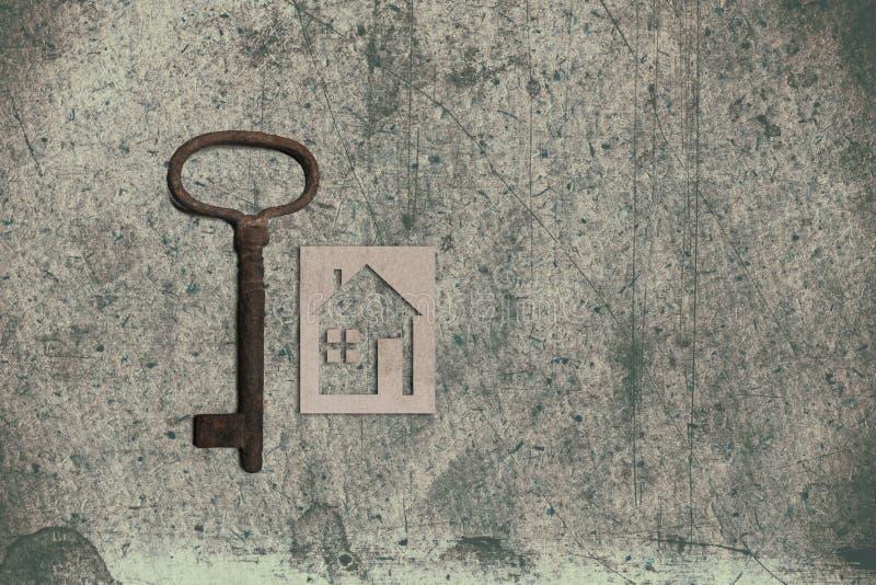 Модель дома картона с ключом на старом текстурированном бумажном backgrou стоковая фотография rf