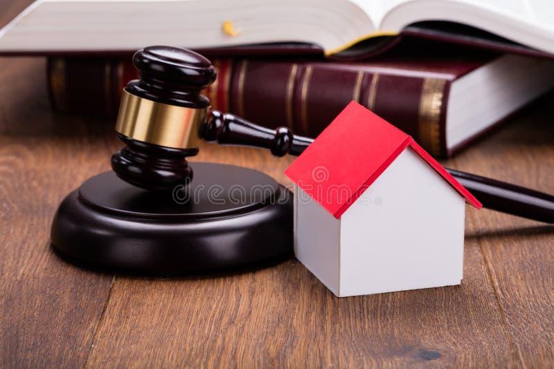 Модель дома с молотком на деревянном столе стоковое фото
