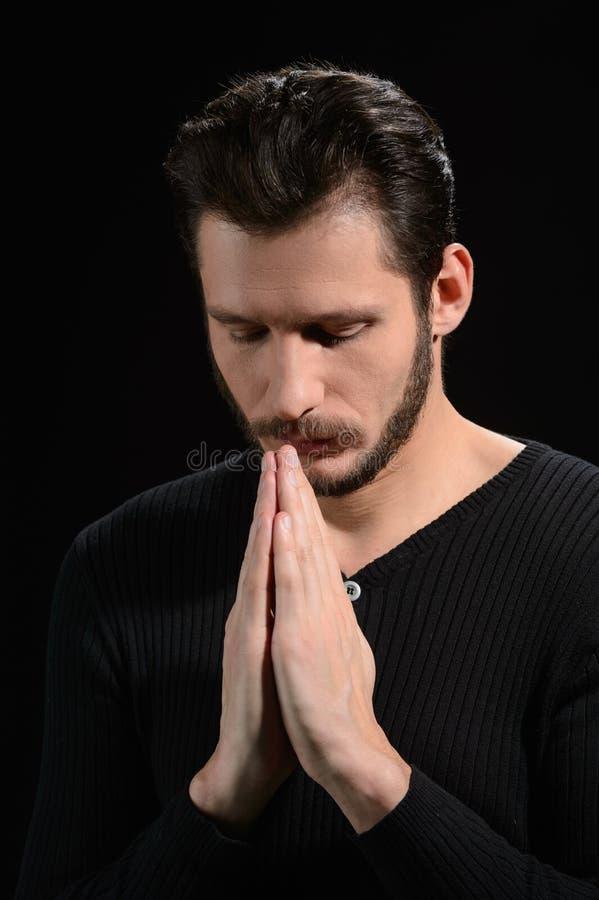 Молить человека. Портрет бородатого человека моля и держа его Хан стоковая фотография rf