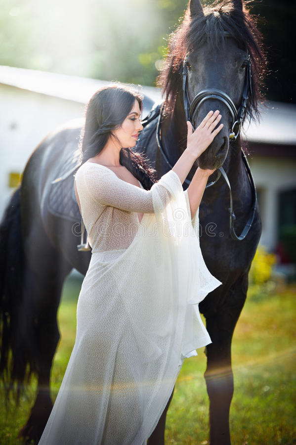 Модная дама с белым bridal платьем около коричневой лошади Красивая молодая женщина в длинном платье представляя с дружелюбной ло стоковые изображения rf