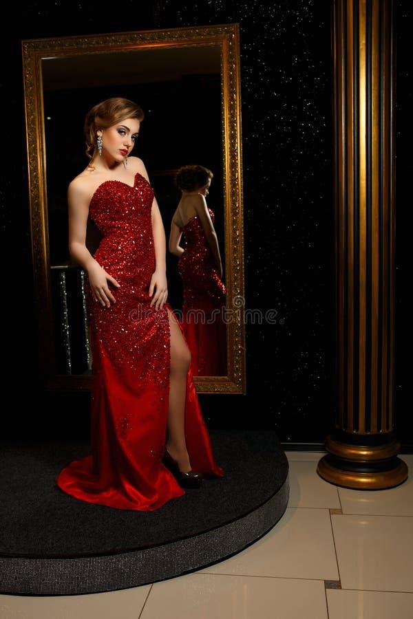 Модная женщина представляя в красной мантии стоковые изображения