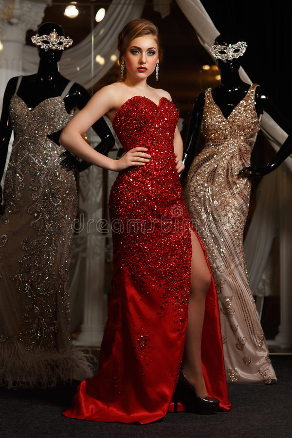 Модная женщина представляя в красной мантии стоковое изображение rf