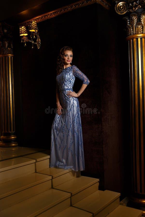Модная женщина стоя на лестницах золота стоковое фото rf